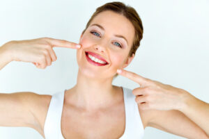 lady with white pearly teeth pointing at them